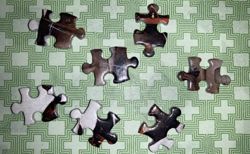 Seven jigsaw puzzle pieces on a green background